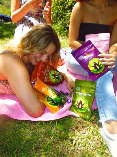 Friends sharing Emerald Sky edibles in the park