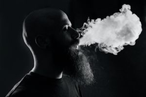 Man blowing out vapor